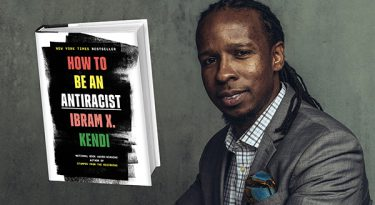 Ibram X. Kendi in a gray suit with his book