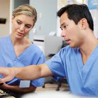 Asian man in scrubs showing White woman in scrubs something on computer at clinic nurses station.